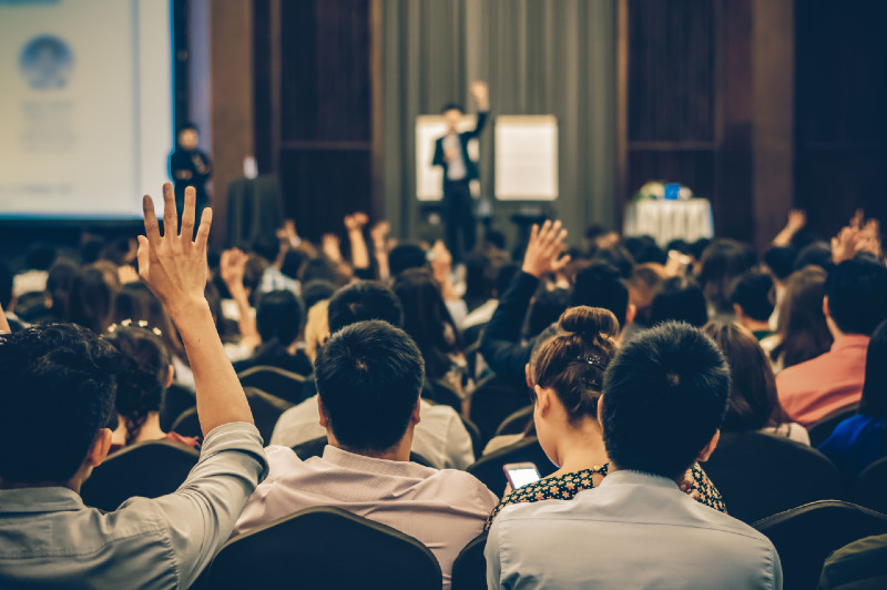 crowd listening to speaker at a conference